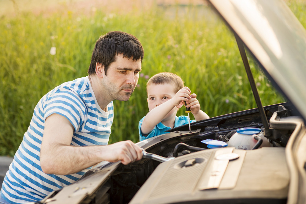Young father with his little son repairing car