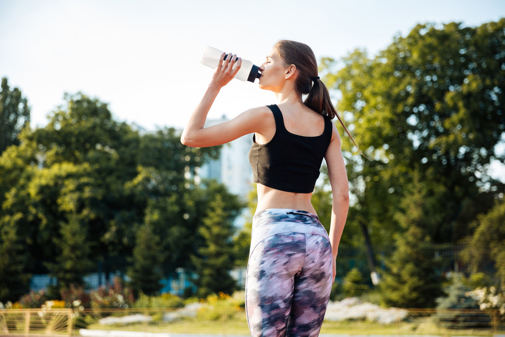 Young female athlete drinking from water bottle after workout at stadium