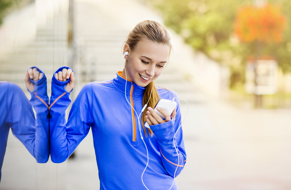 Young female runner is having break and listening to music during the run in city center