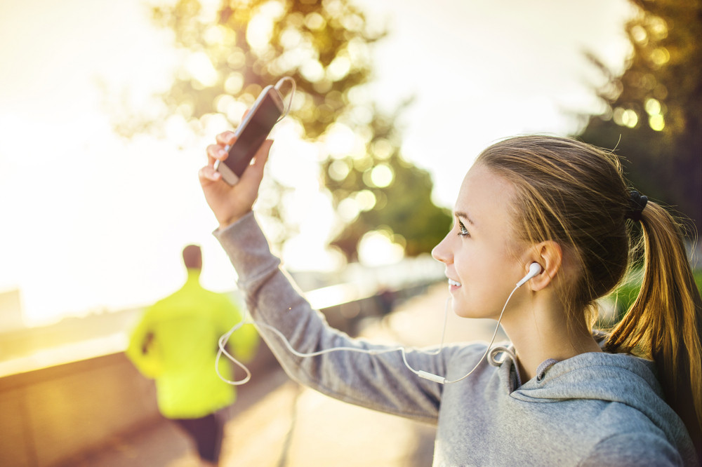 Young female runner is having break and taking selfie during the run in city on a quay