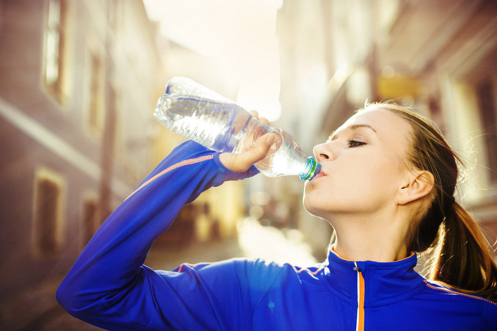 Young female runner is having break, drinking water during the run in city center