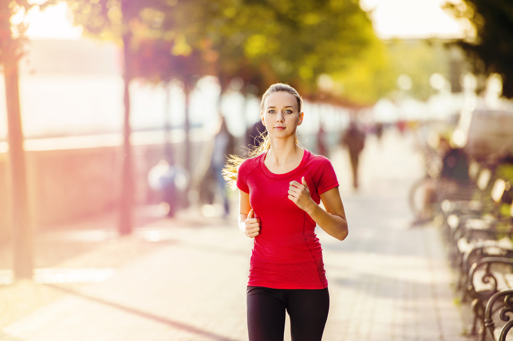 Young female runner is jogging in the city on a quay. Sport lifestyle.