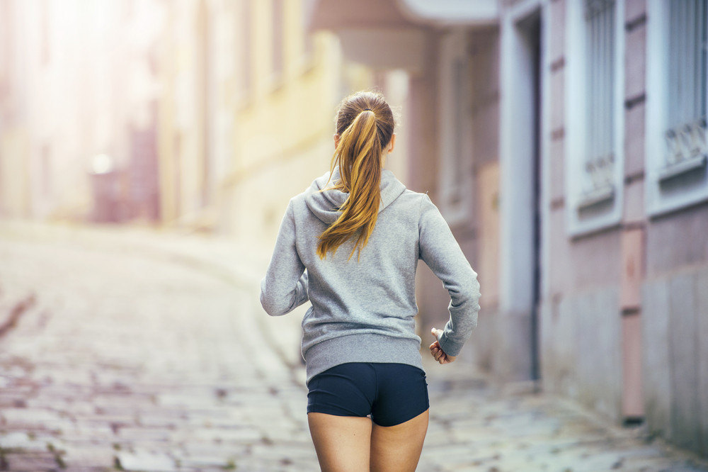 Young female runner is jogging on tiled pavement old city on center. Healthy lifestyle.