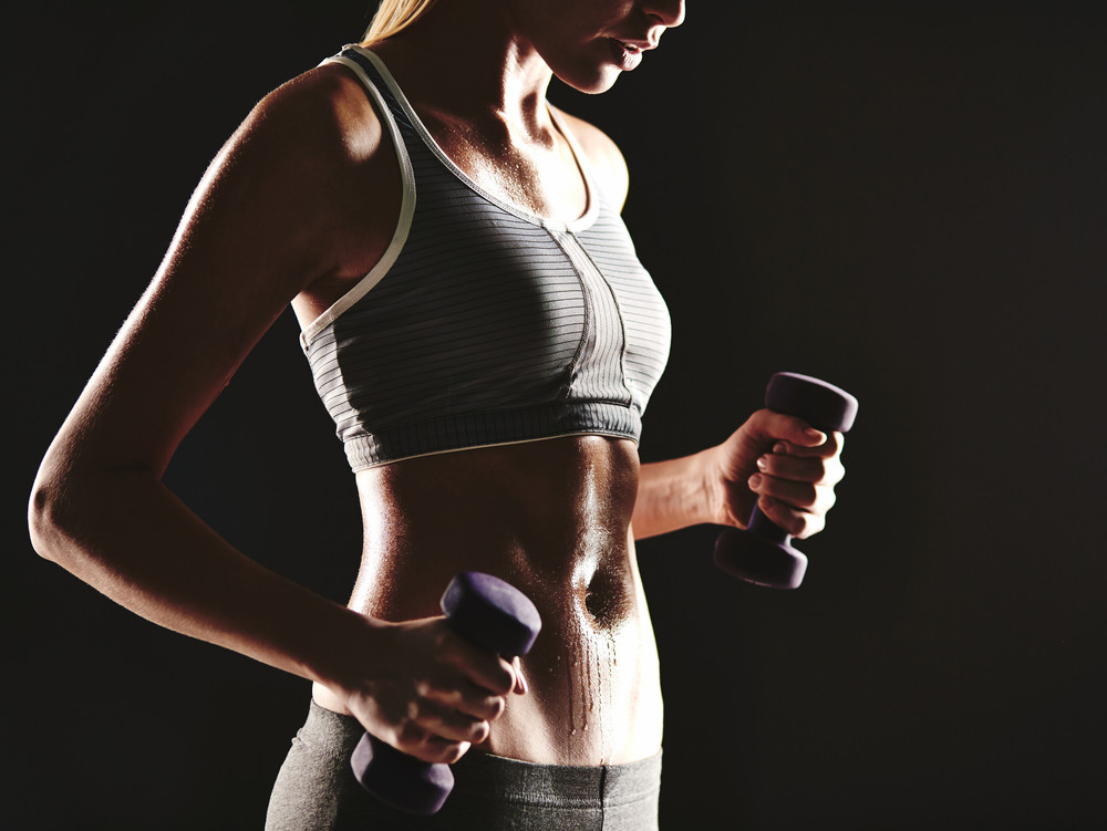 Young female training with dumbbells in isolation
