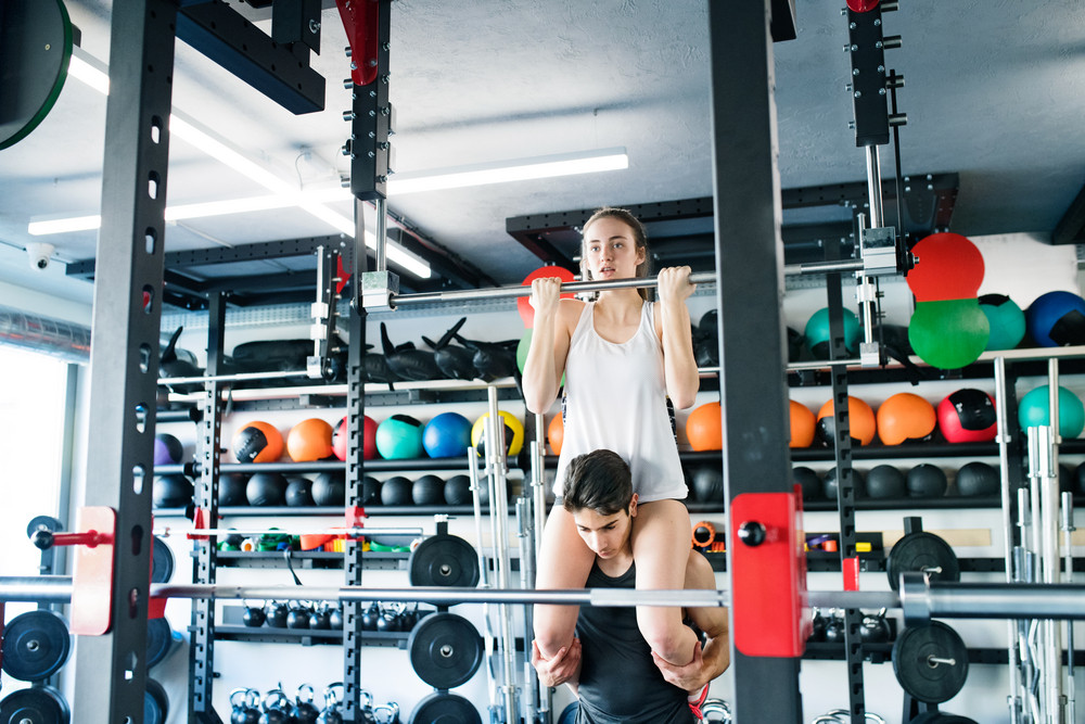 Young fit couple in modern crossfit gym exercising. Woman doing pull ups, man carrying her on his shoulders.