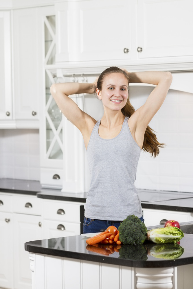 Young fit / healthy / sporty woman wash / prepare vegetables and fruit. Modern and exclusive kitchen.