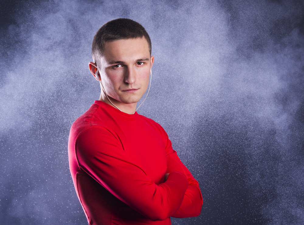 Young fitness athlete is posing in studio with black background.