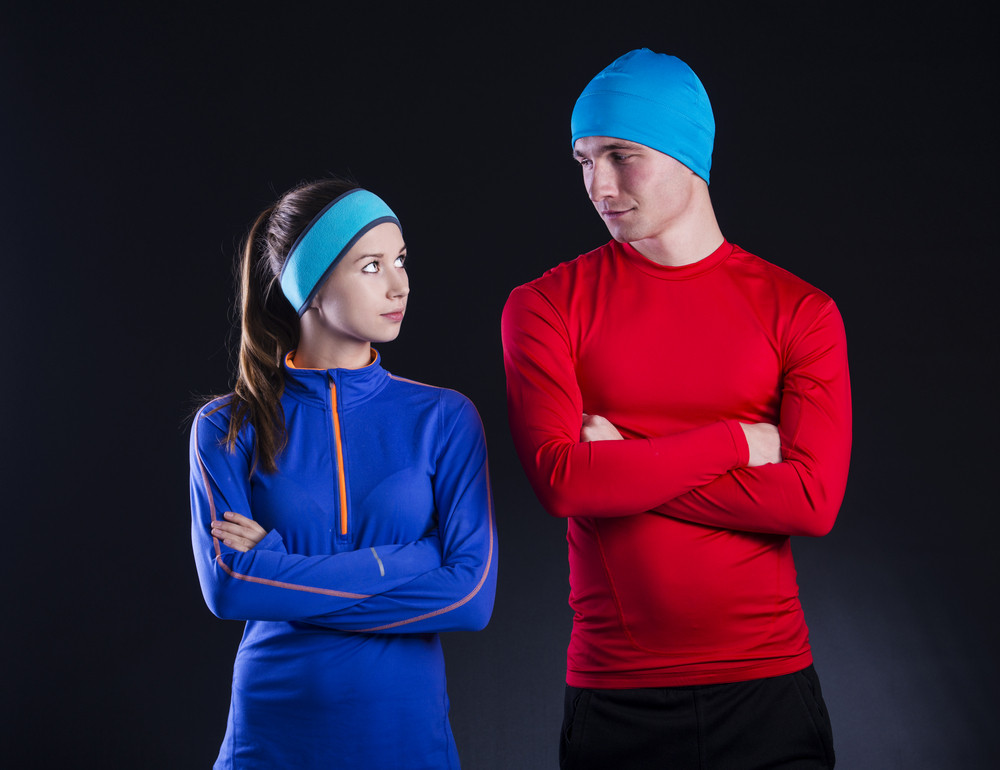 Young fitness athletes are posing in studio with black background. They are dressed in winter sportswear.