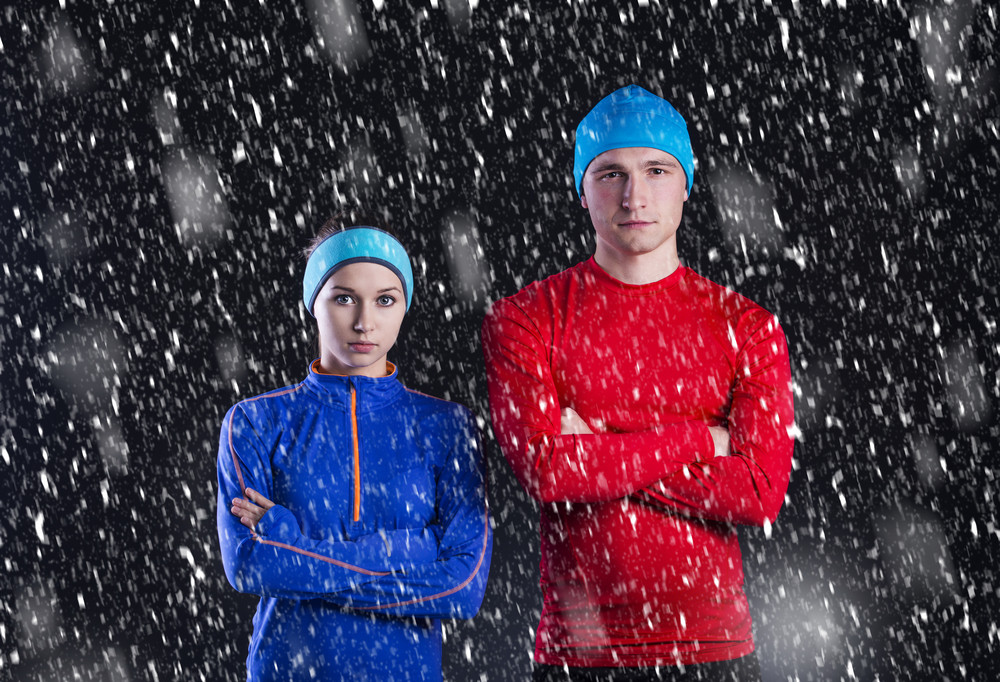 Young fitness athletes are standing outside in cold winter night. Snow is falling around.