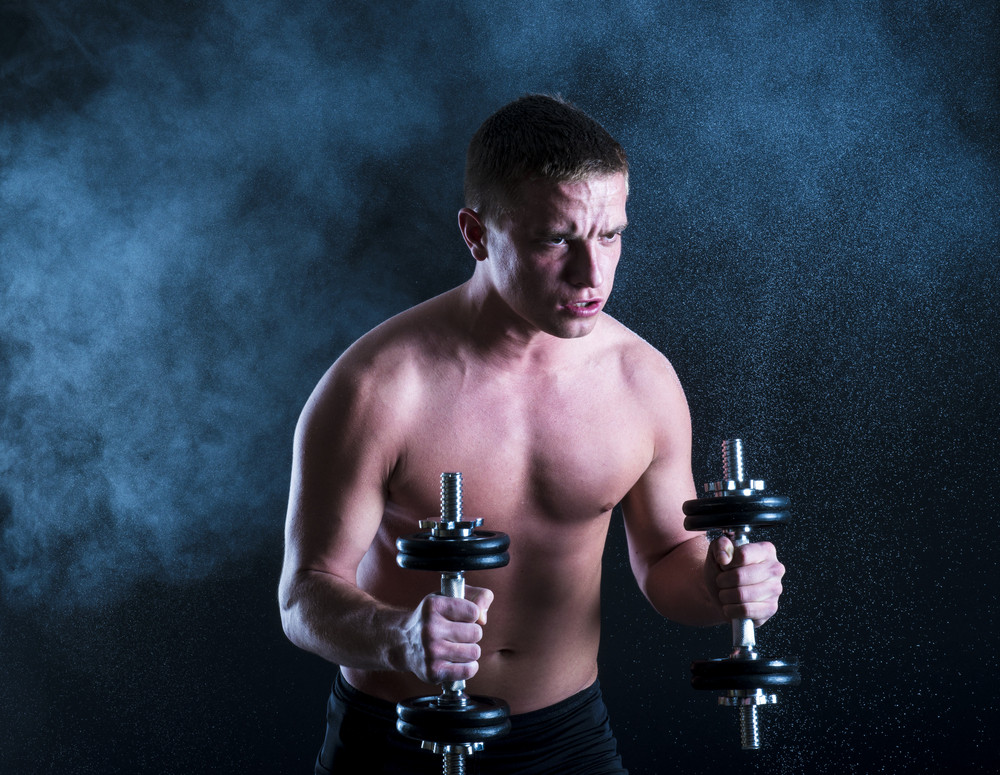 Young fitness model is posing in studio