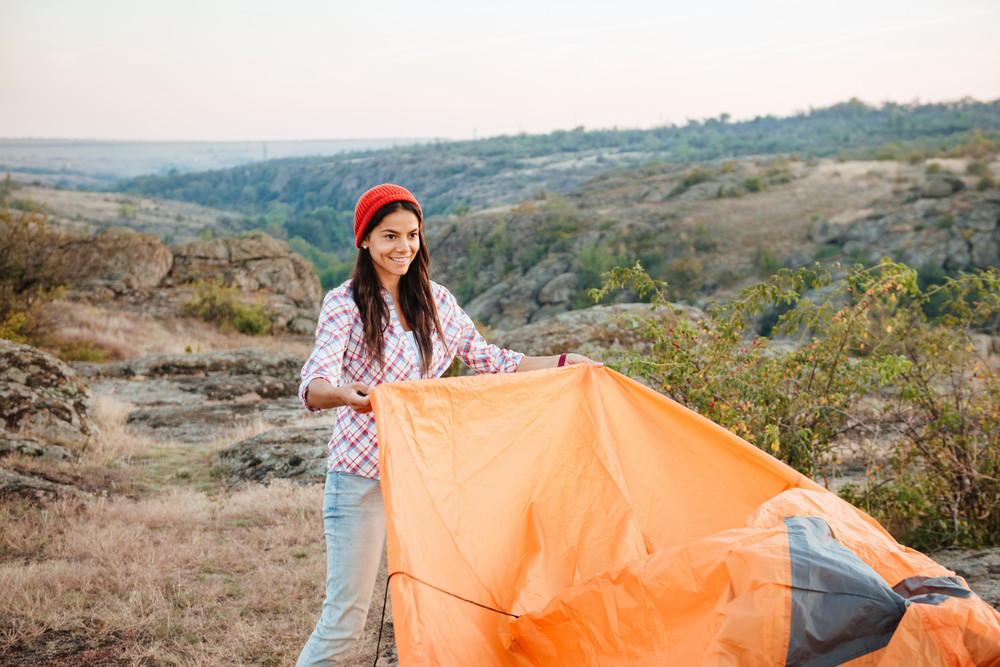Young gril collect tent on mountain
