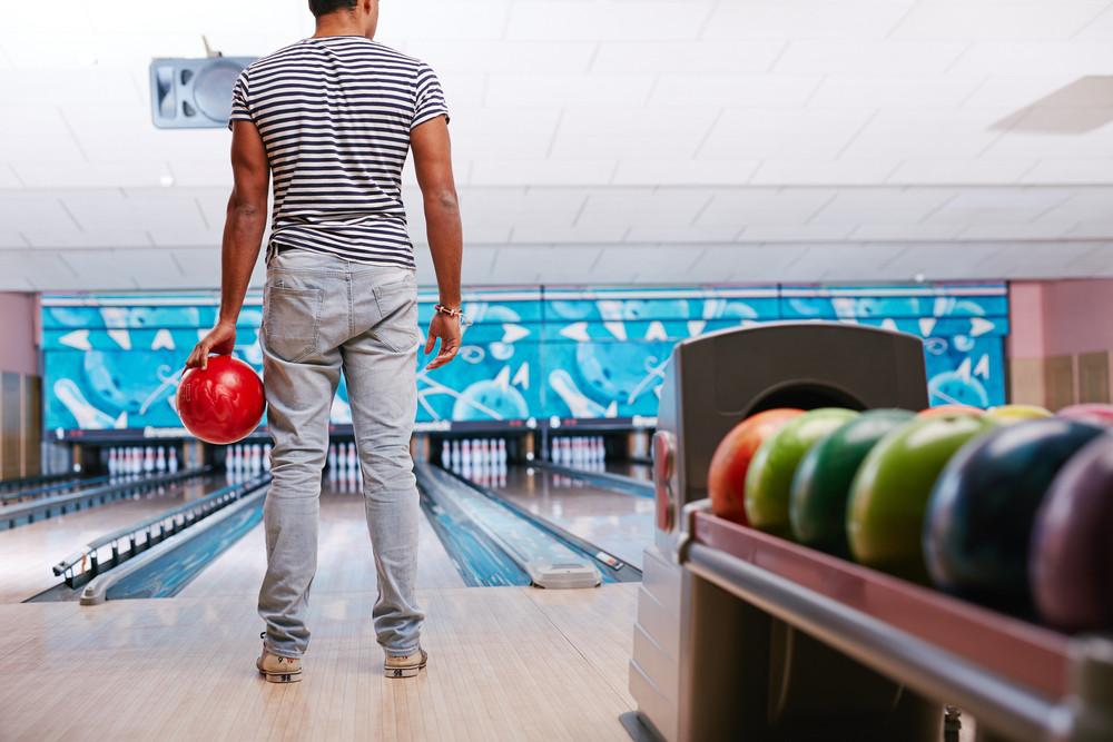 Young guy in casualwear playing bowling