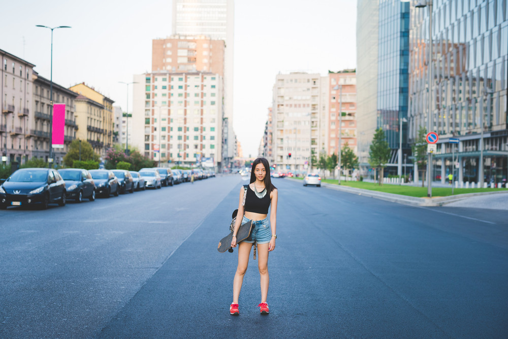 Young handsome asiatic long brown straight hair woman skater posing in the middle of the street in the city, looking in camera, pensive - thinking future, serious, thoughtful concept