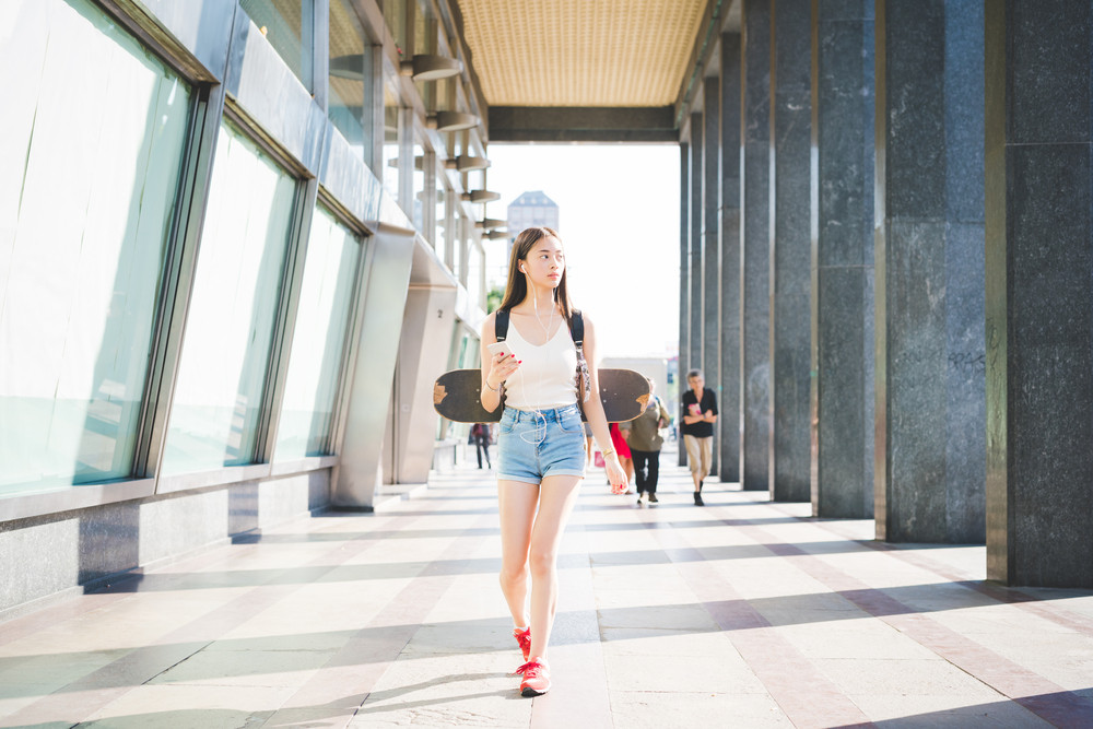 Young handsome asiatic long brown straight hair woman skater walking in the city, listening music with earphones and holding a smartphone, overlooking left, pensive - thinking future, relaxing concept