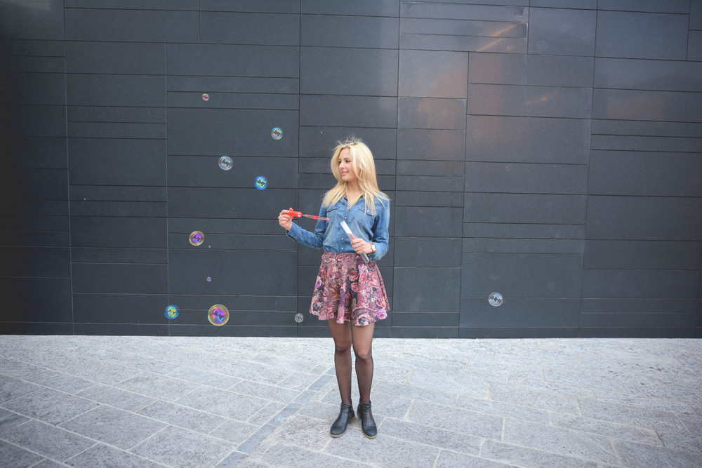 Young handsome blonde caucasian girl having fun playing with soap bubble in the city wearing jeans shirt and floral skirt - emancipation, carefreeness, youth concept