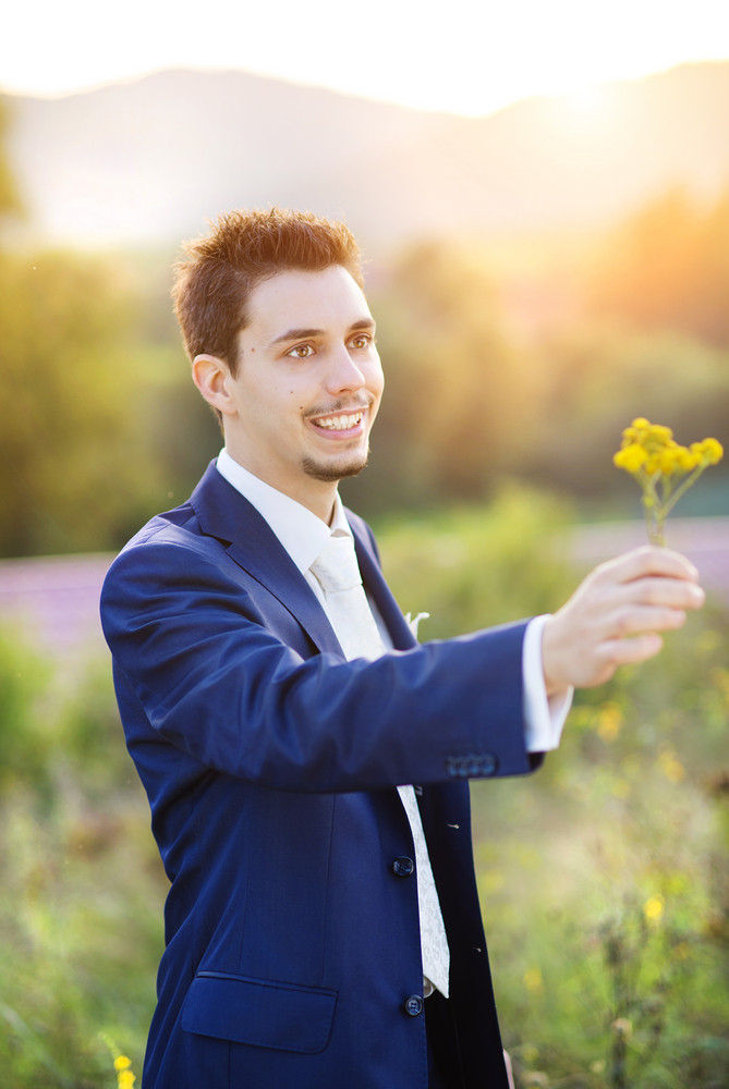 Young handsome bridegroom giving a flower to his bride outside in a summer park.