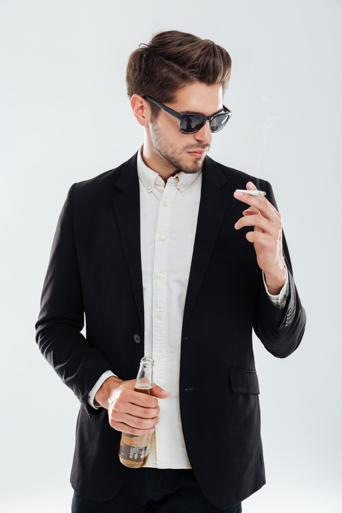 Young handsome businessman in sunglasses holding beer bottle and smoking cigarette over gray background