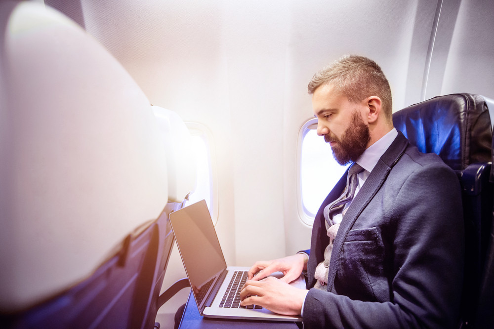 Young handsome businessman with notebook sitting inside an airplane
