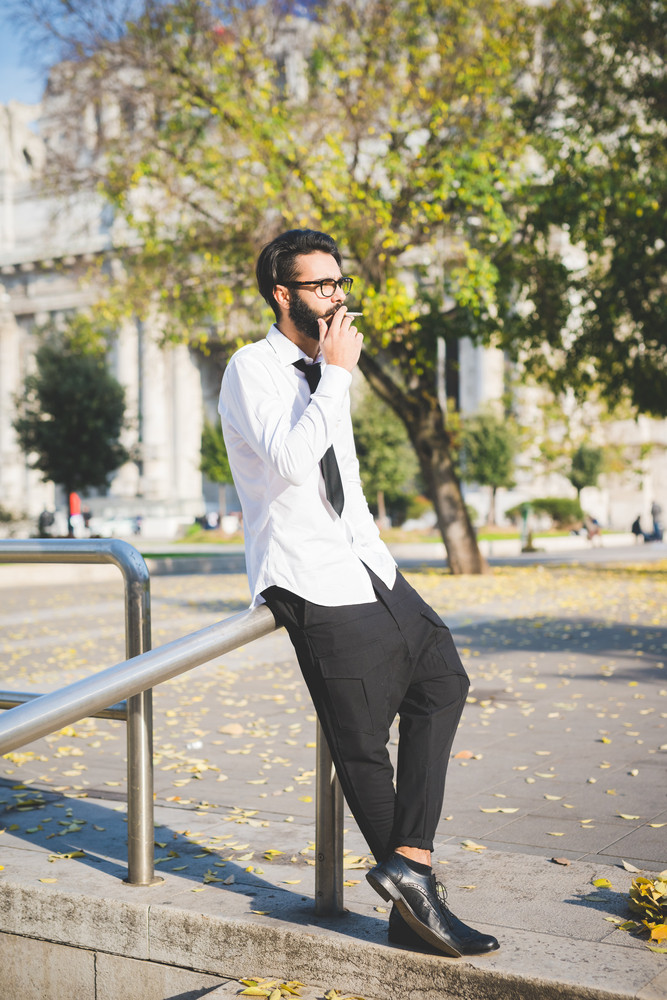 young handsome caucasian bearded businessman walking outdoor in the street, overlooking pensive smoking cigarette - business, thoughtful, serious concept