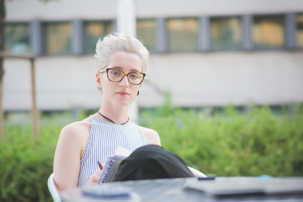 young handsome caucasian blonde italian designer sitting in a bar with sketchbook on her leg, looking in camera, pensive - youth, creativity concept - dress with striped shirt
