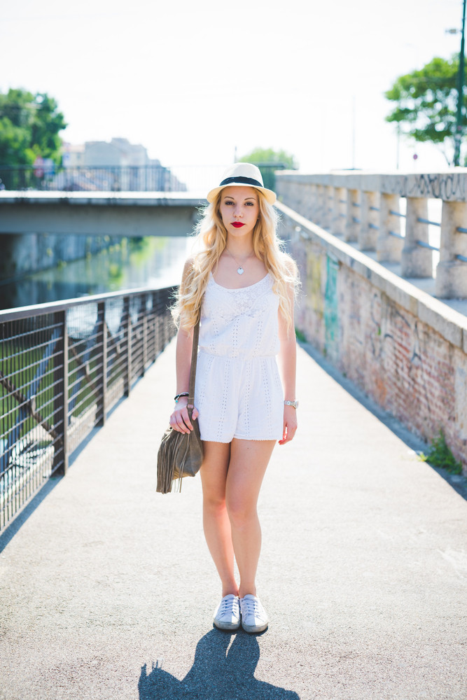Young handsome caucasian blonde straight long hair woman posing in the city, looking in camera, wearing panama hat, white dress and holding a bag - freshness, youth, carefreeness concept