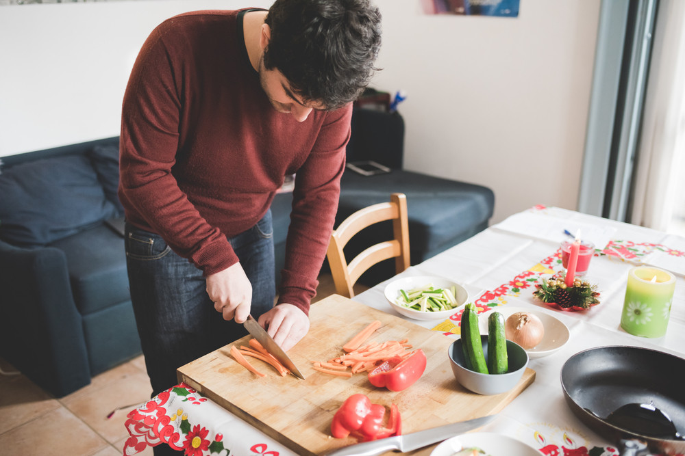 Young handsome caucasian brown hair man cutting some carrots with knife on a cutting board, surrounding by bowl, vegetables, pan and knife - healthy, veggie, food concept