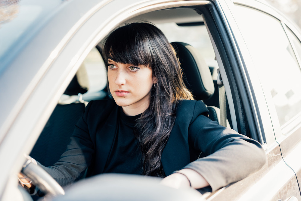 young handsome caucasian brown hair woman sitting on his car driving, looking straight, serene - traveling, transport concept