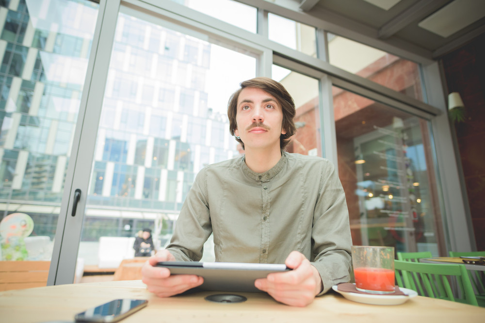 Young handsome caucasian man with moustache seated on a bar using technological devices like smartphone and tablet overlooking - technology, communication, social network concept