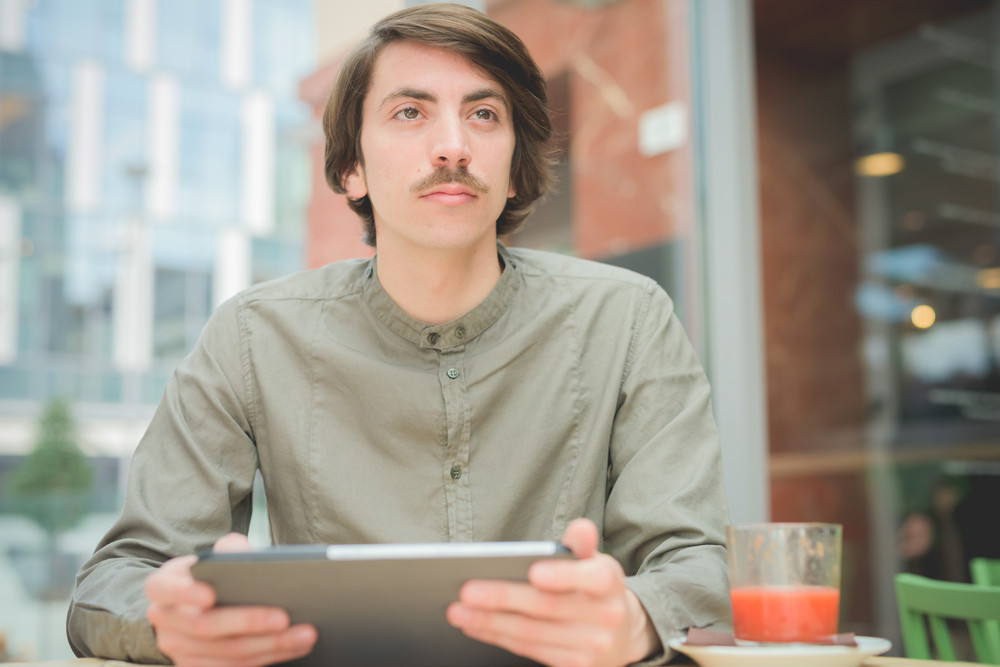 Young handsome caucasian man with moustache seated on a bar using technological devices like tablet overlooking- technology, communication, social network concept