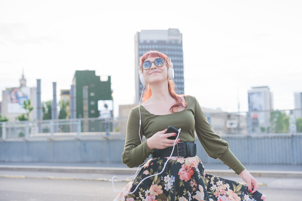 Young handsome caucasian redhead woman listening music with headphones and smartphone, dancing in the city, smiling - relaxing, dancing, carefreeness concept