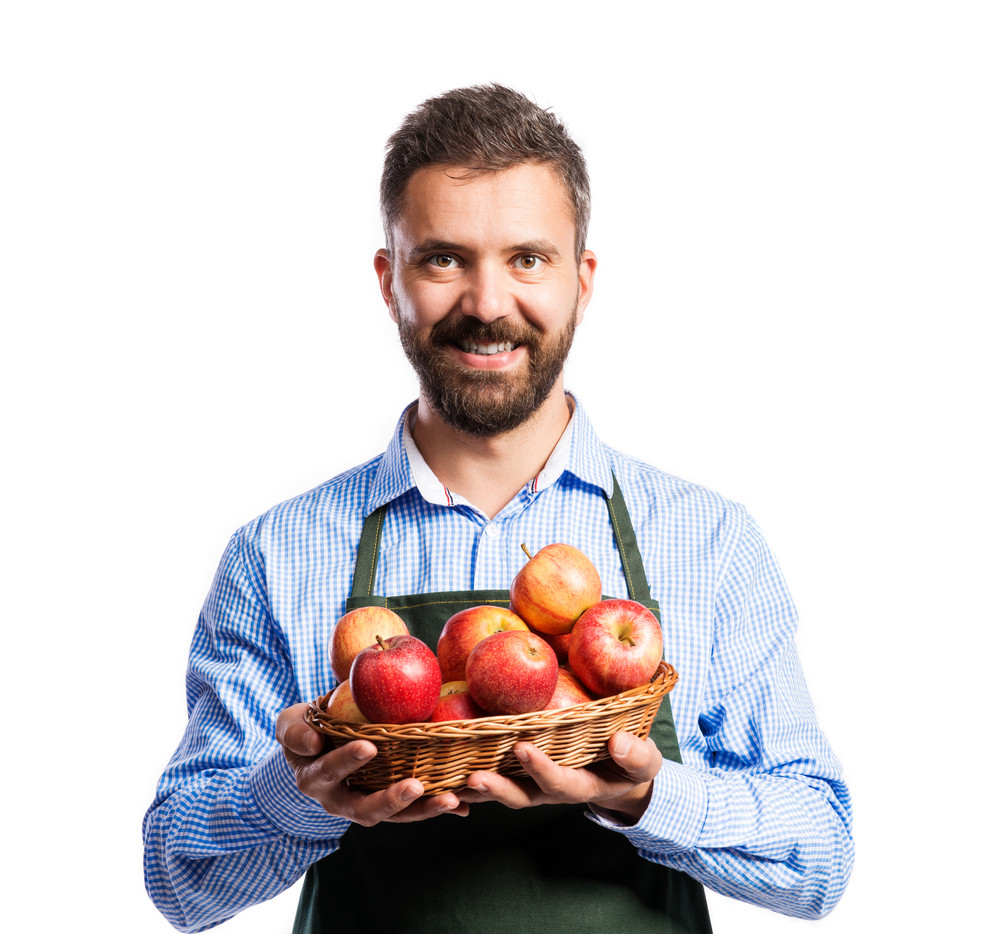 Young handsome gardener holding a basket full of apples. Studio shot on white background