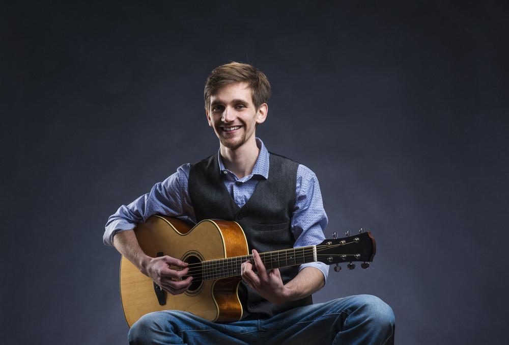 Young handsome guitar player. Studio shot on black background.