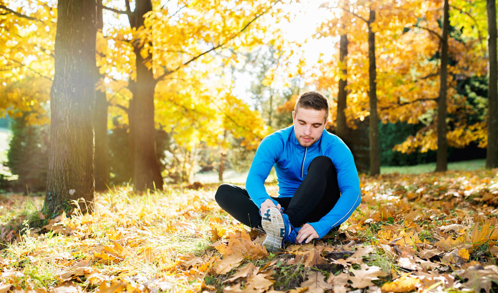 Young handsome hipster runner in blue sweatshirt outside in colorful sunny autumn nature sitting on the ground, tying shoelaces