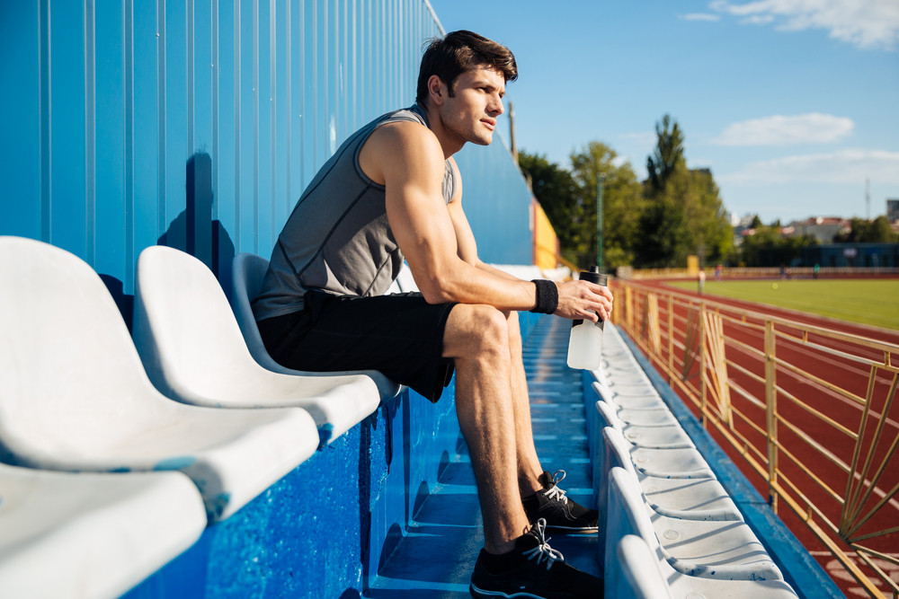 Young handsome male athlete resting after workout and holding water bottle at the stadium