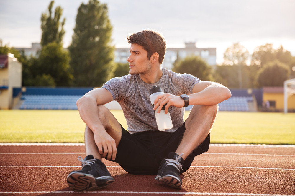 Young handsome man athlete resting at the stadium and drinking water, looking away