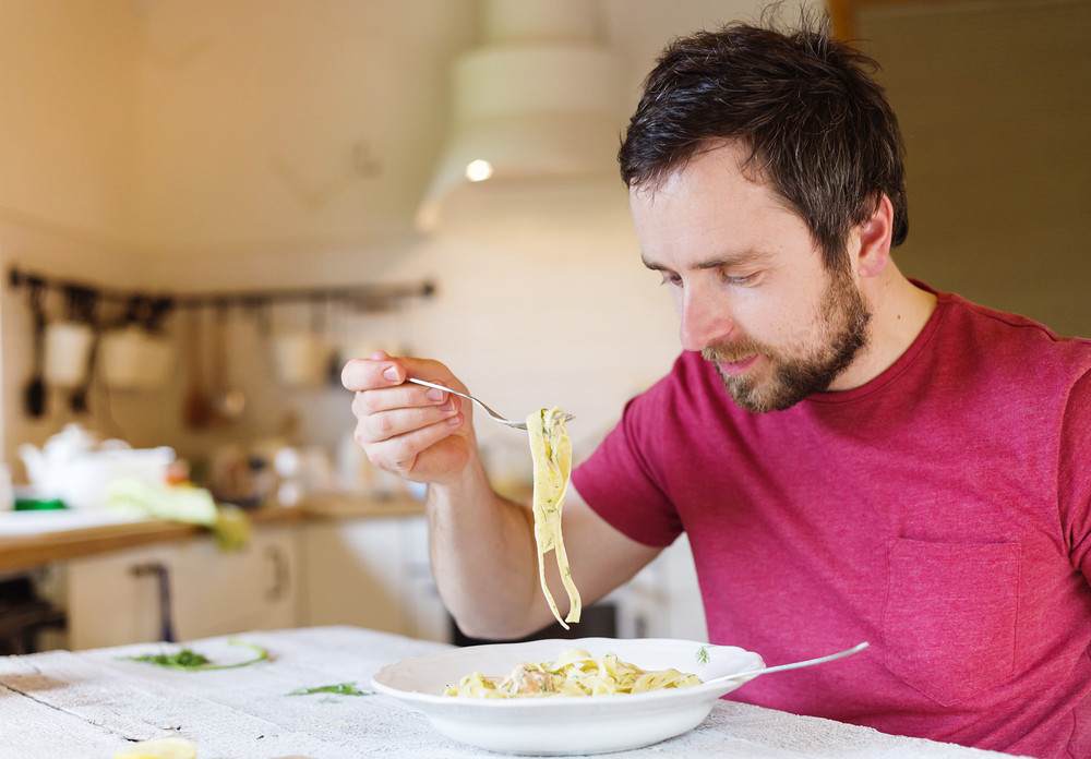 Young handsome man in the kitchen eating salmon tagliatelle