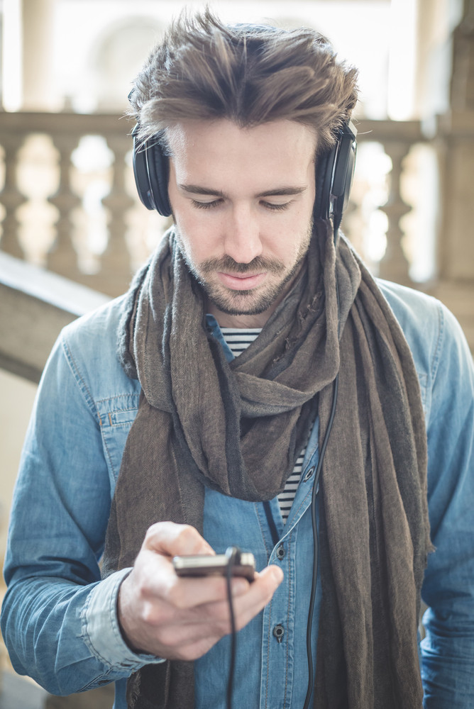 young handsome man listening to music with headphones  outdoors