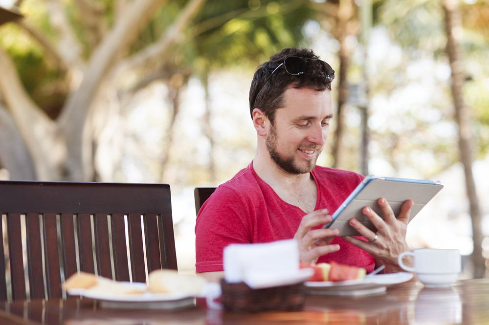Young handsome man relaxing and using digital tablet