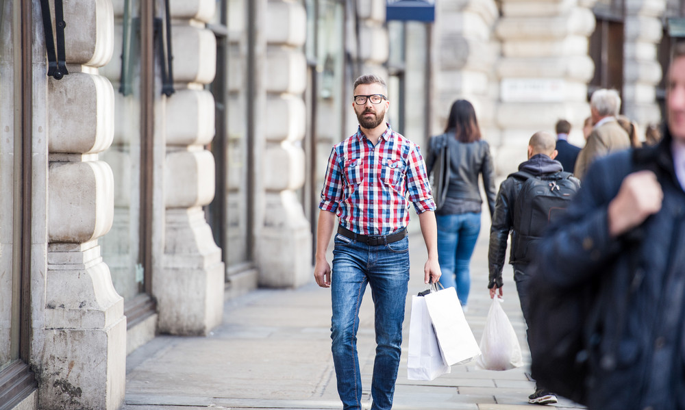 Young handsome man shopping in the streets of London