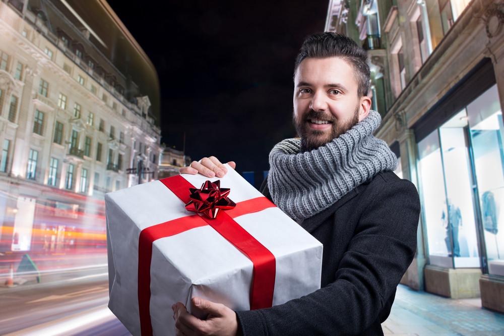 Young handsome man with Christmas present in the city