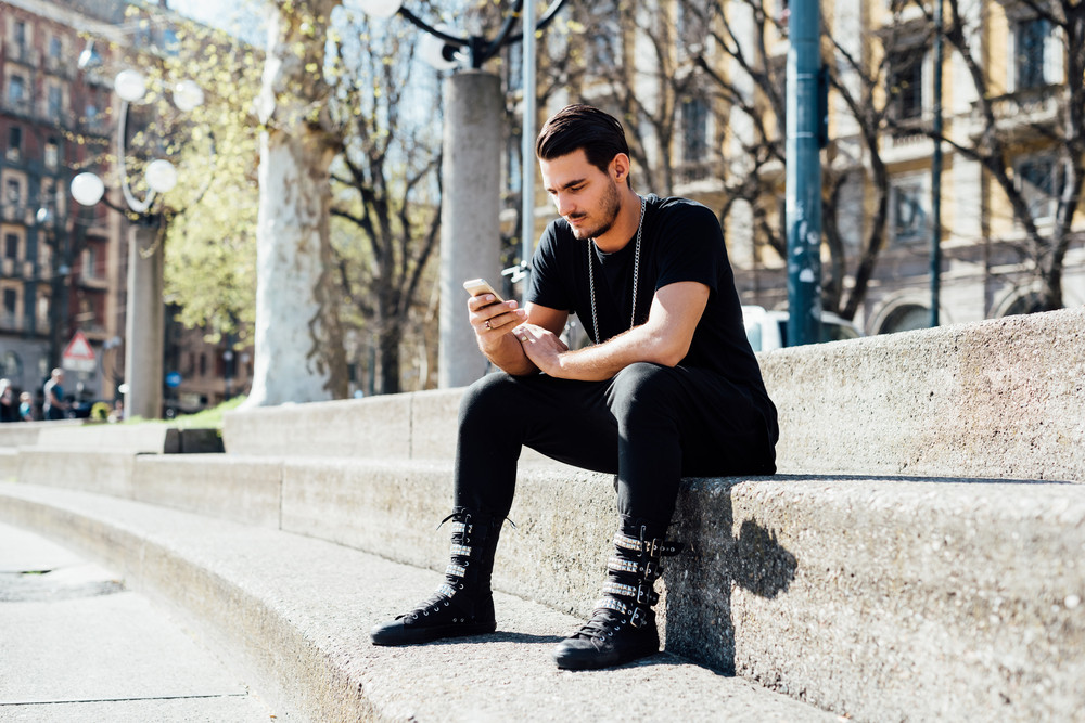 Young handsome mllennial man seated on a sidewalk using a smartphone tapping the screen - social network, technology, communication concept