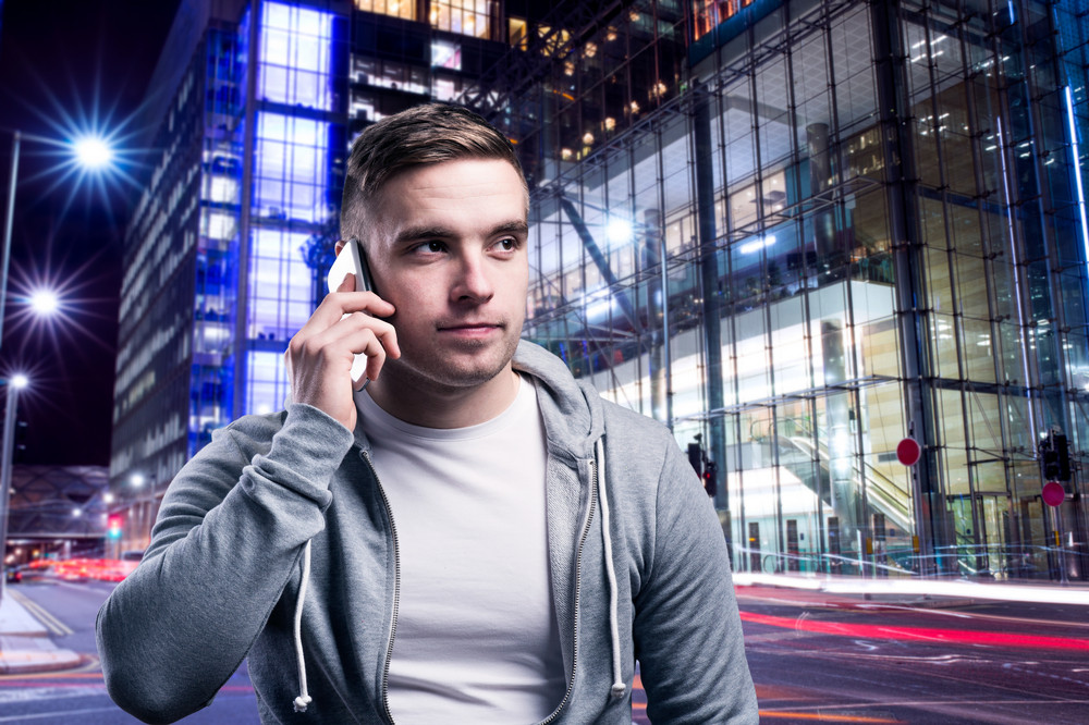 Young handsome runner with smart phone in the night city
