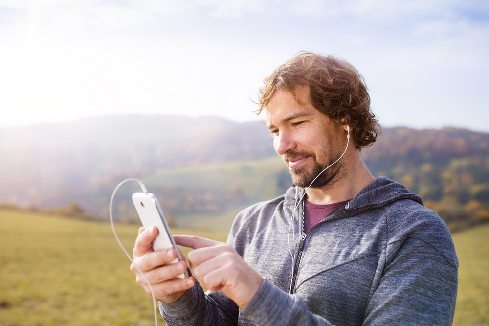 Young handsome runner with smart phone outside in sunny autumn nature