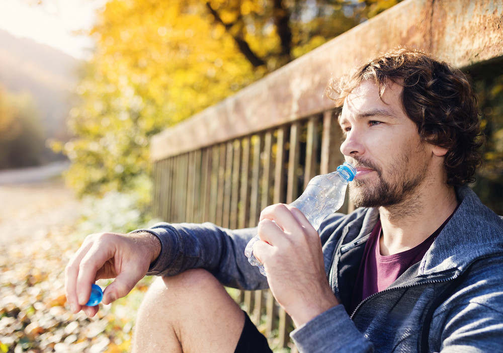 Young handsome runner with water bottle sitting on a bridge