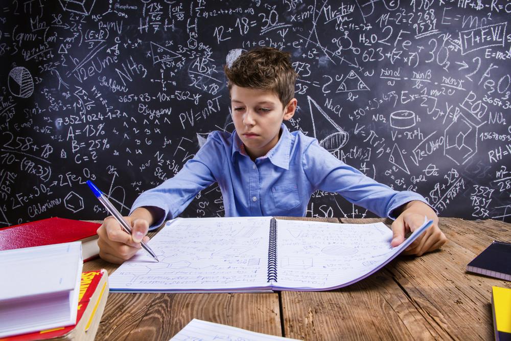 Young handsome school boy doing his homework in front of big blackboard