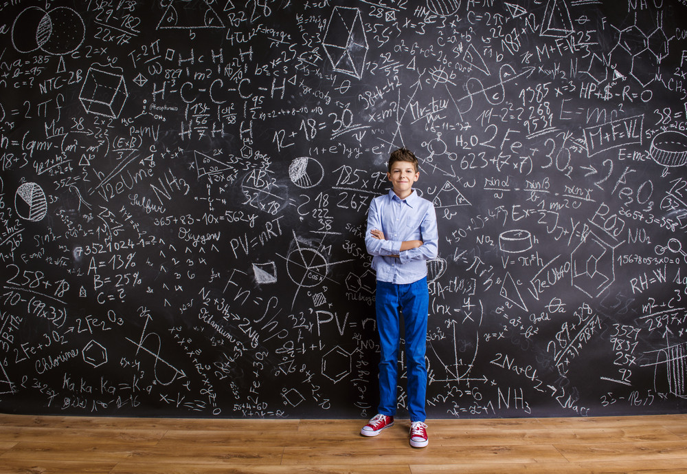 Young handsome school boy standing in front of big blackboard