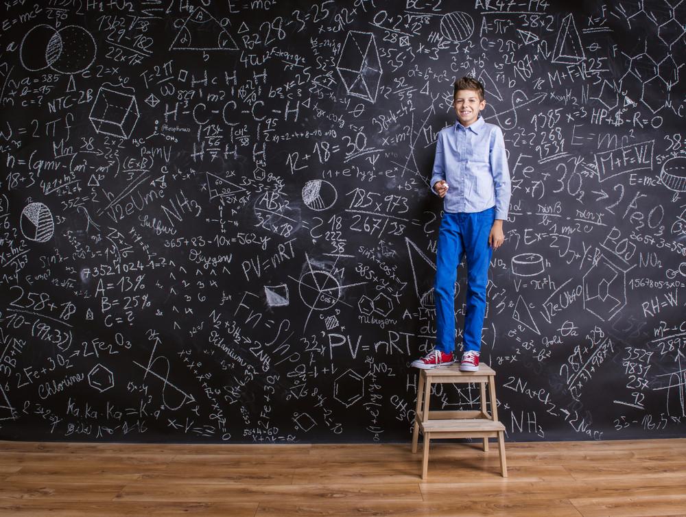 Young handsome school boy standing in front of big blackboard