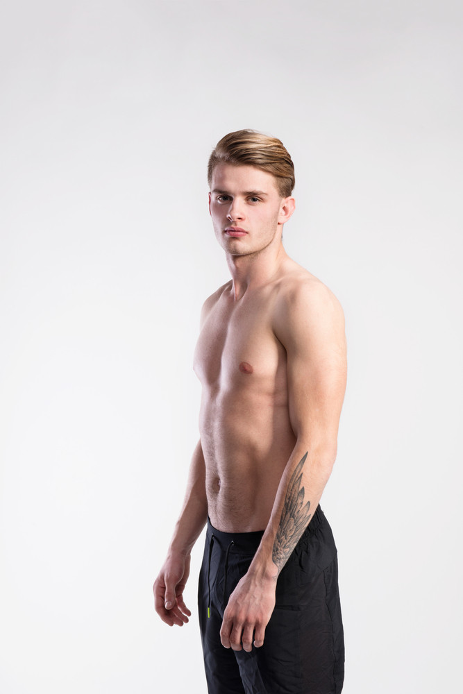 Young handsome shirtless fitness man. Studio shot on gray background.