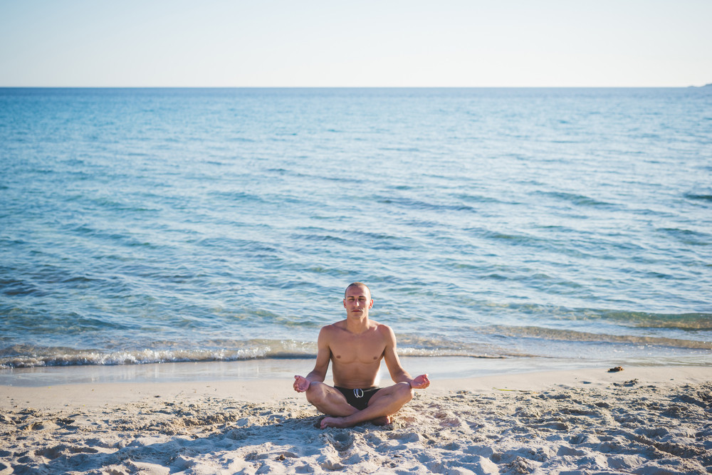 young handsome sporty man making yoga at the beach in summertime in lotus position from front - meditation, relaxing, wellness concept