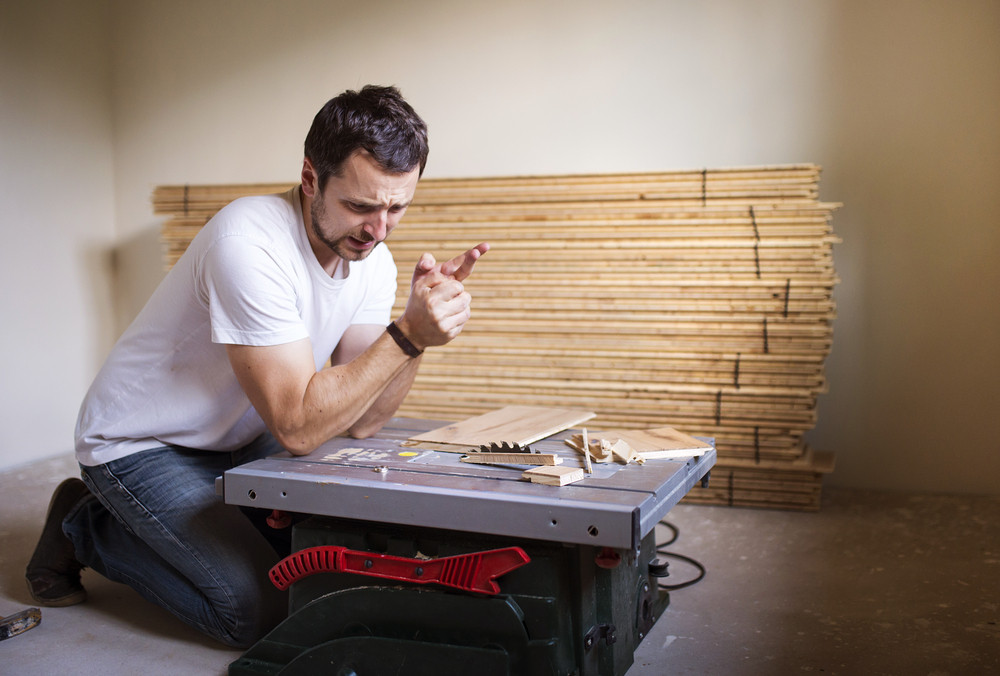 Young handyman having accident during cutting plywood on circular saw